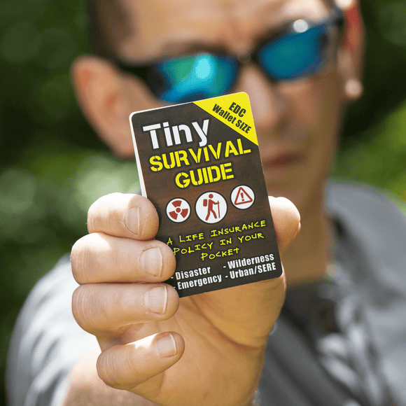 Tiny survival guide in a mans hand
