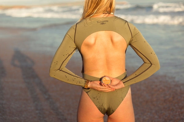 guide to spf - woman holding natural sunscreen before surf