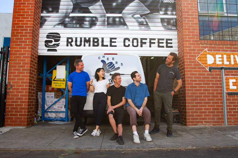 The Rumble Coffee Team Laughing out the front of the roller door to their Roastery