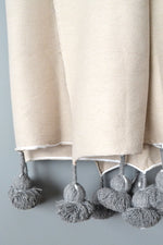 Natural Cotton Throw With Steel Gray Pom Poms from Yuba Mercantile