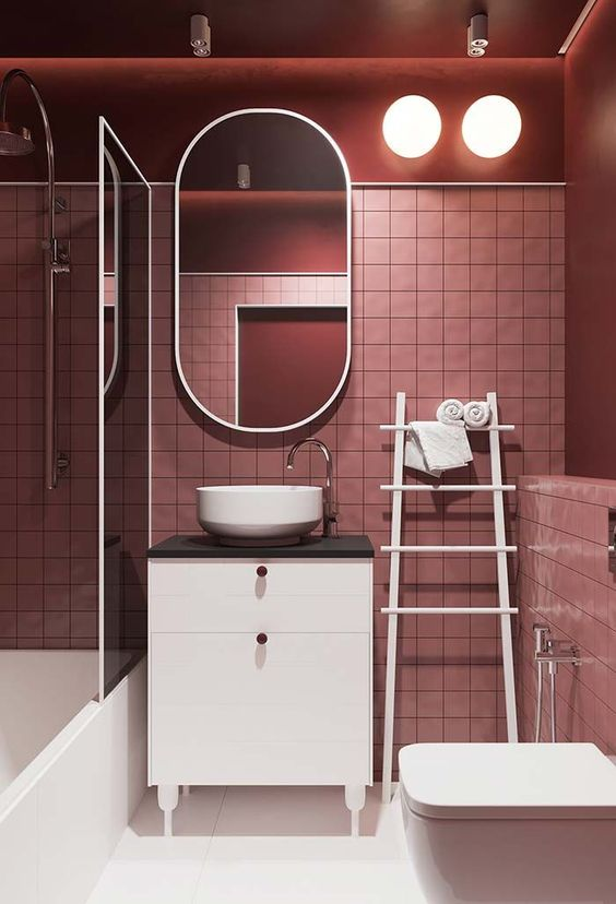 Paired wall lights in pink bathroom