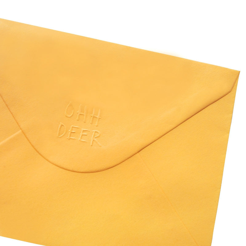 Back of yellow envelope with Ohh Deer logo embossed