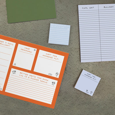 Orange deskpad on table with lined deskpad and two post-it notes on table