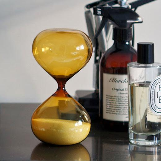 Gold coloured hourglass timer with sand at bottom, on shelf with bottles in background