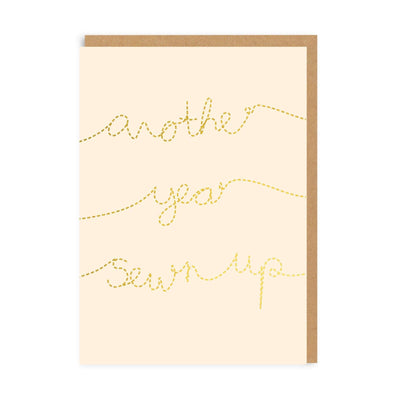 Pale pink birthday card with gold text imitating sewing with 'Another Year sewn up' text