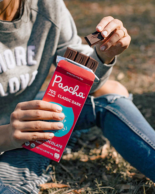 Woman holding Pascha 70% Cacao Organic Dark Chocolate Bar outside on the grass