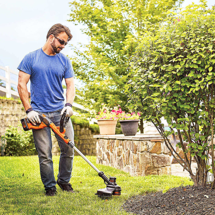man using the Black and Decker LST140C String Trimmer in the front yard