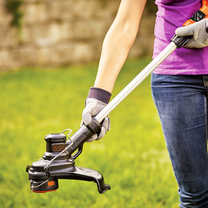woman extending the Black and Decker LST140C String Trimmer