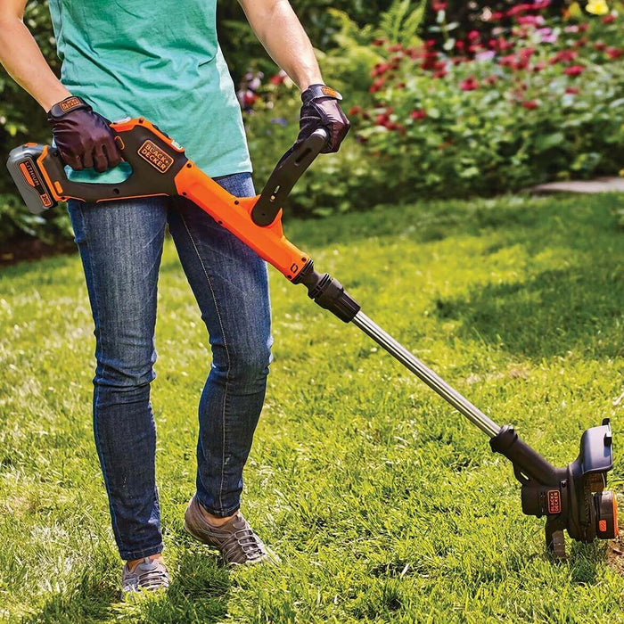 person using the Black and Decker LSTE523 String Trimmer in the yard