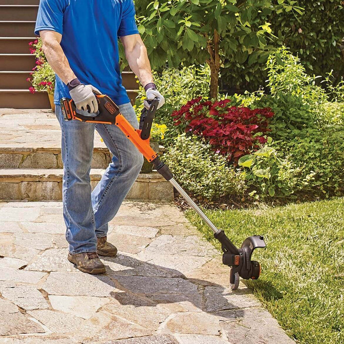 person using Black and Deck LSTE525 String Trimmer on side walk
