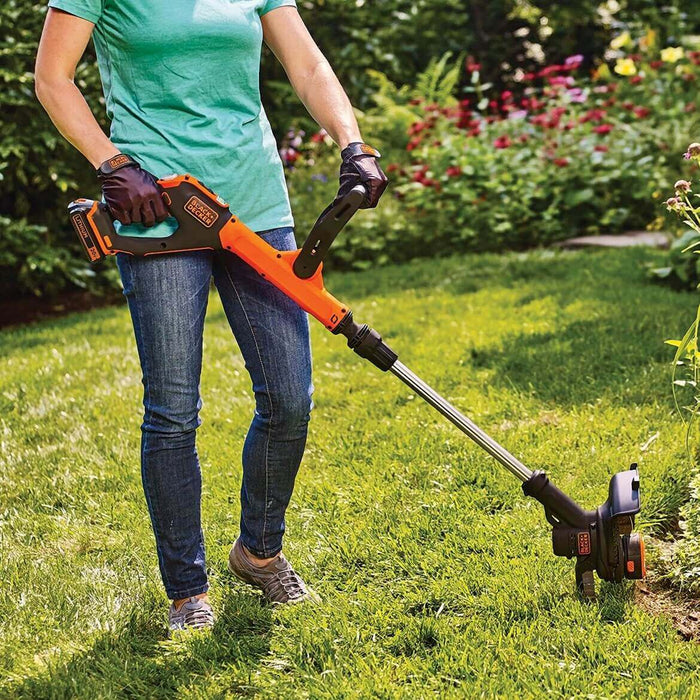 person using Black and Deck LSTE525 String Trimmer on lawn