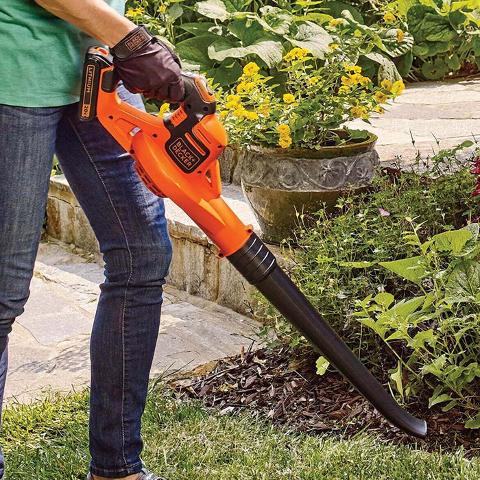 person using the Black and Decker LSW321 Leaf Blower in the garden