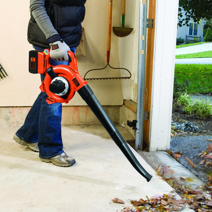 person suing the Black and Decker LSWV36 Sweeper Blower in the garage