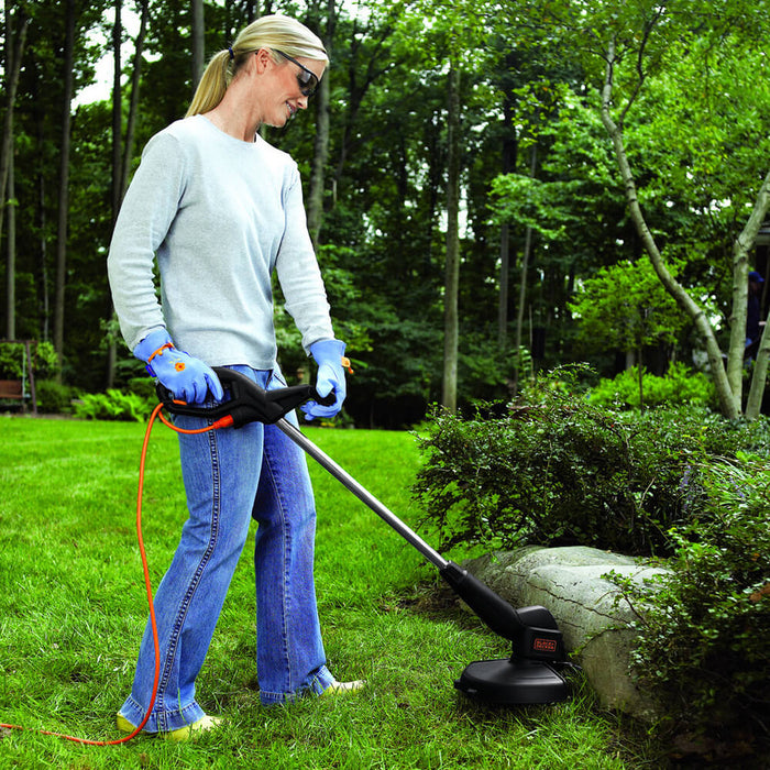 woman using the Black and Decker ST4500 Electric String Trimmer