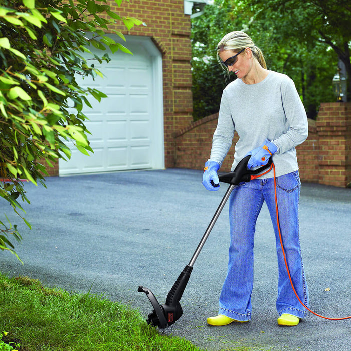 woman using the Black and Decker ST4500 Electric String Trimmer on the driveway grass