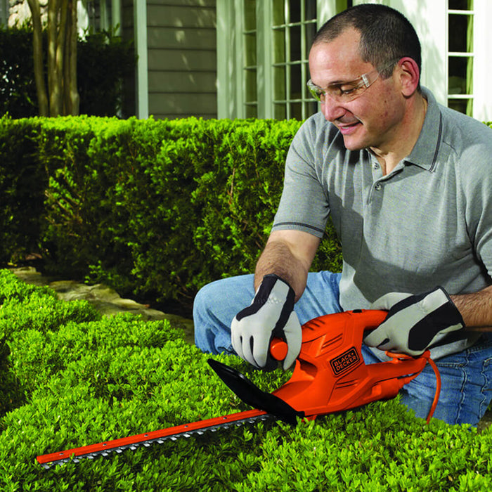 someone trimming a bush with the TR117 black and decker hedge trimmer kneeling