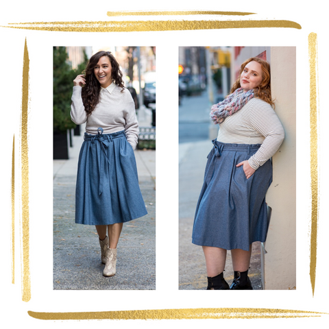 Woman on left wears light grey sweater layered over cream blouse, paired with knee length blue-grey skirt with 3 pleats and paperbag pleating at waistline and matching belt tied in a bow. Woman on right wears same skirt paired with black and white striped shirt with large chunky knit pastel scarf