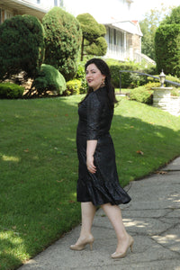 side view of size 10 woman wearing A-line dress with side ruffles