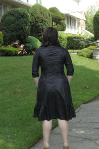 back view of size 10 woman wearing A-line dress with side ruffles