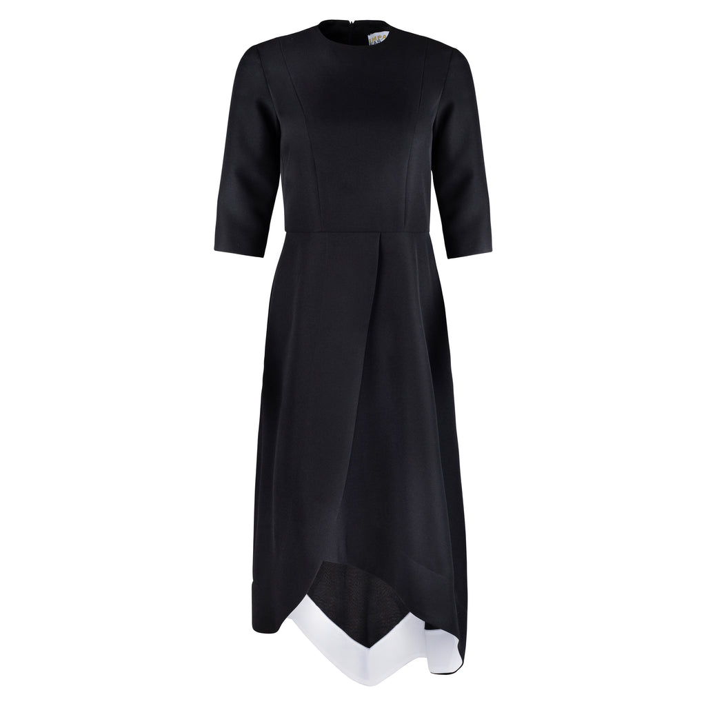 front view of black dress with crew neckline, three quarter sleeves that cover the elbow and faux wrap skirt. The skirt has an asymmetrical design that comes to a point slightly off center back and a white facing inside the hem.