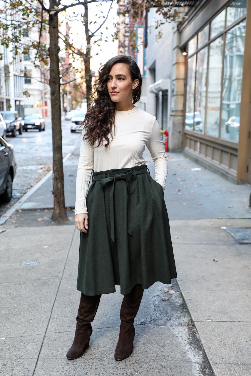 woman wearing pleated skirt with paper bag detailing at waist and matching belt
