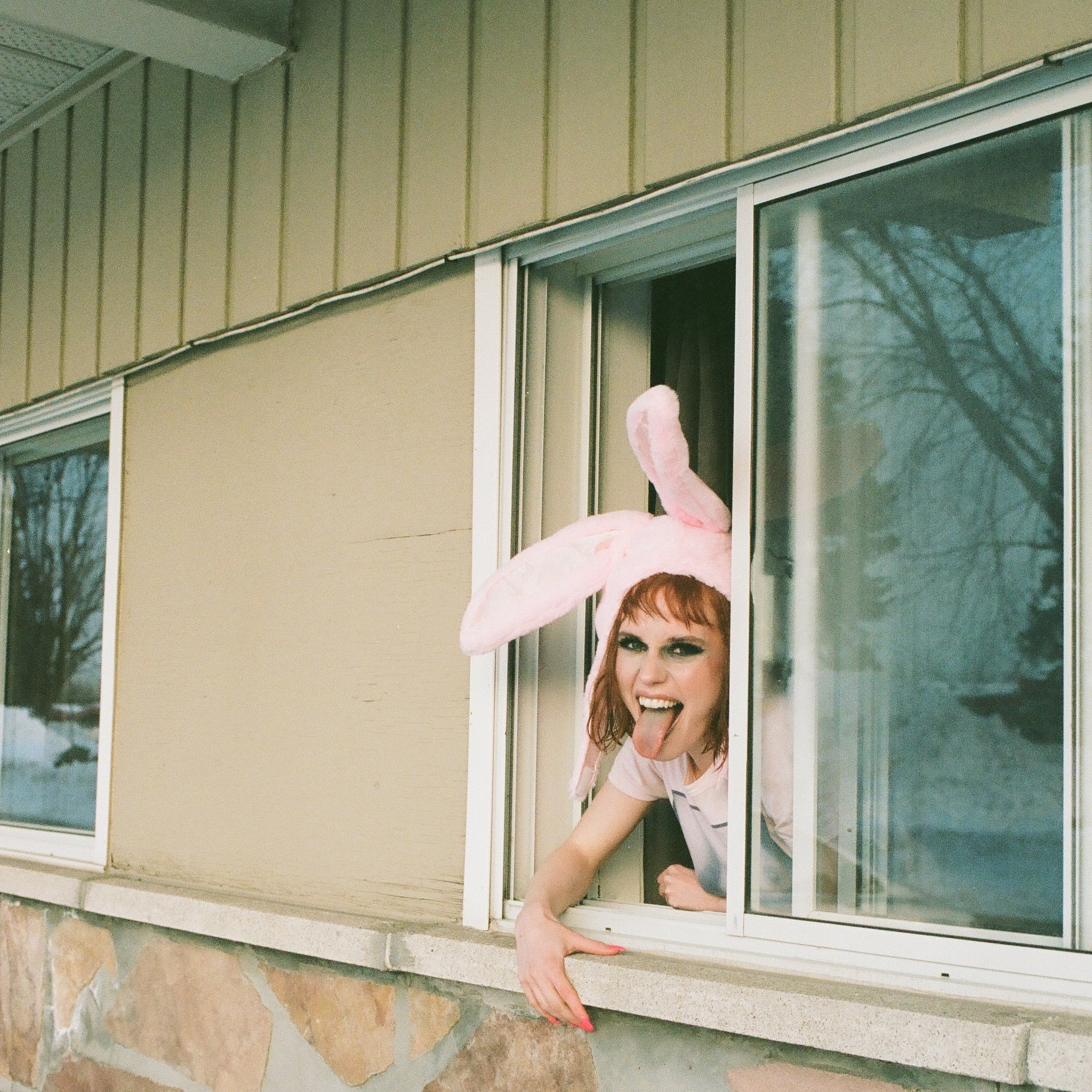 Madelline montreal artist wearing bunny ears out of a motel window, being rebellious