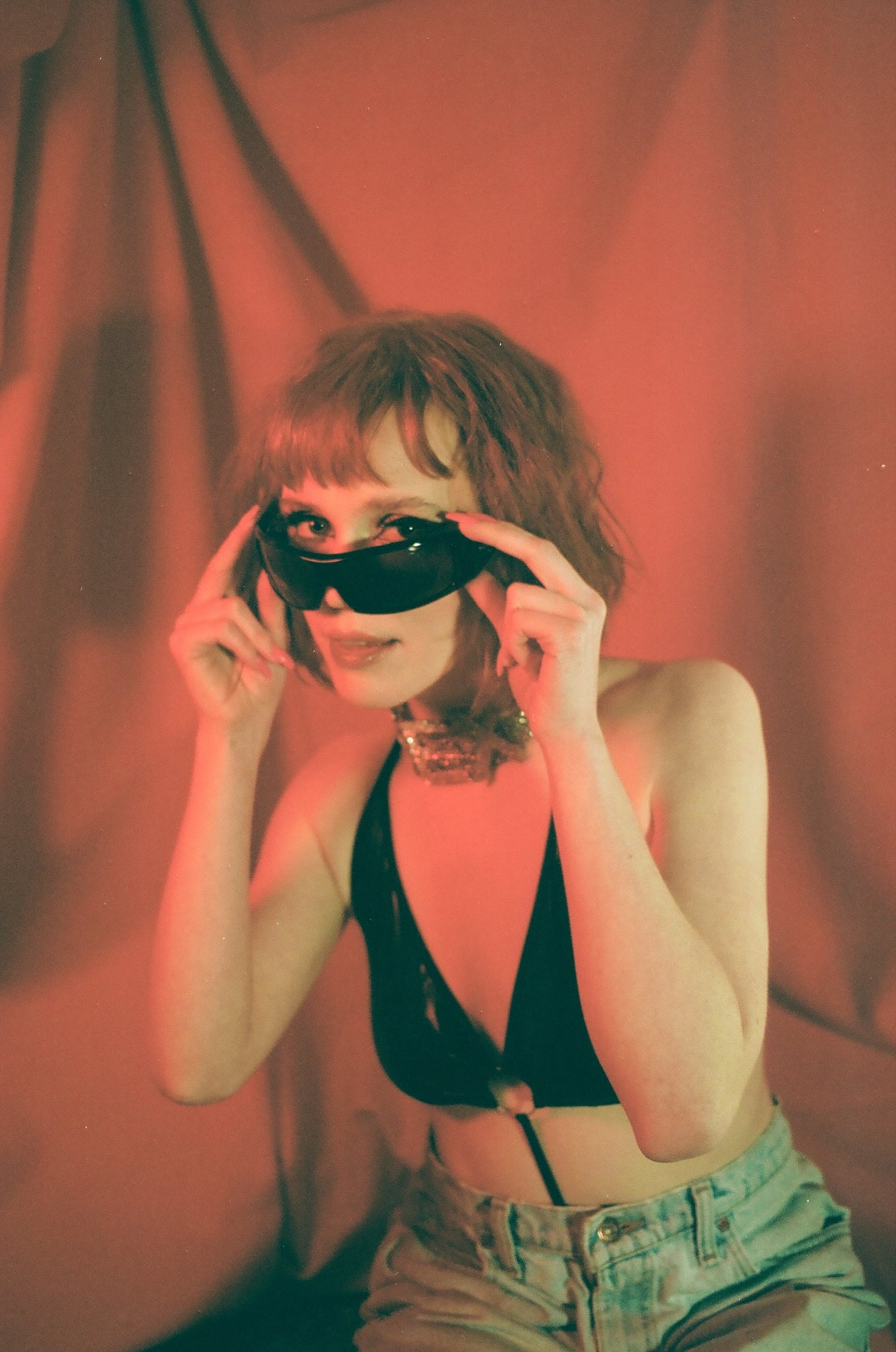 Montreal musician Madelline trying on sunglasses in a red lighting with a blacn bralette and mom jeans