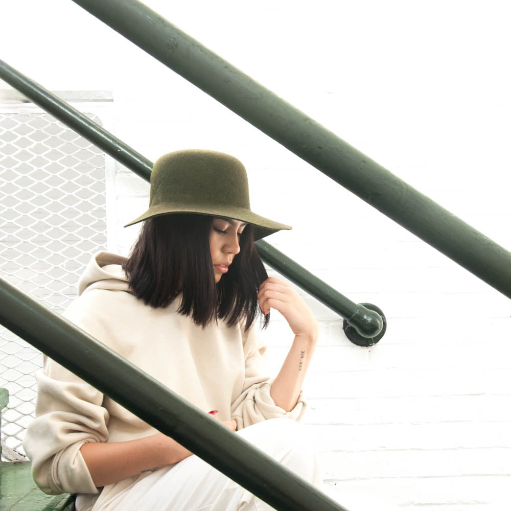 In this editorial, Aleyssa wear a beige hoodie with a green felt hat.