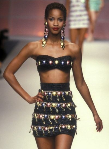 Black model in a fashion couture runway wearing a sparkling outfit.