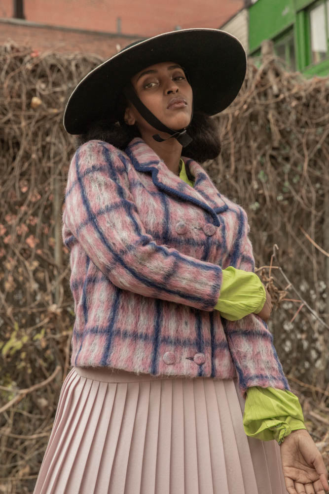 Nicole Musoni for Camille Côté, wearing a vintage style outfit and a wide brim felt hat with a sporty chin strap.