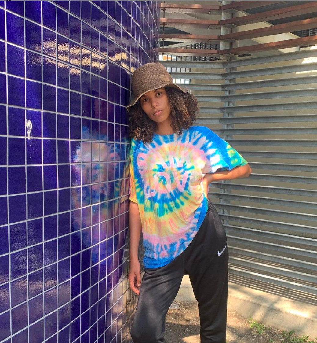 Curly hair model wearing a tie-dye shirt with a straw hat, taking off @alohayalie's Instagram account