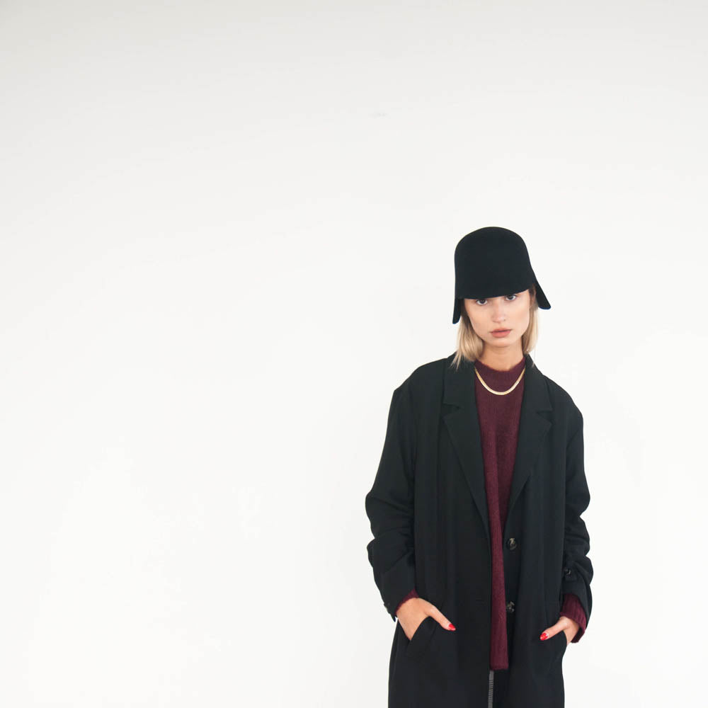 Hands in pockets, the model wears a warm black felt hat.