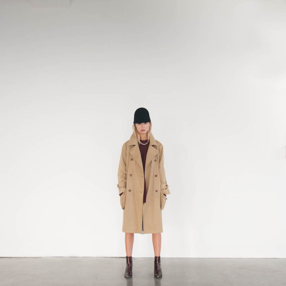 Andrea for Camille Côté wears a beige coat and a black hat.