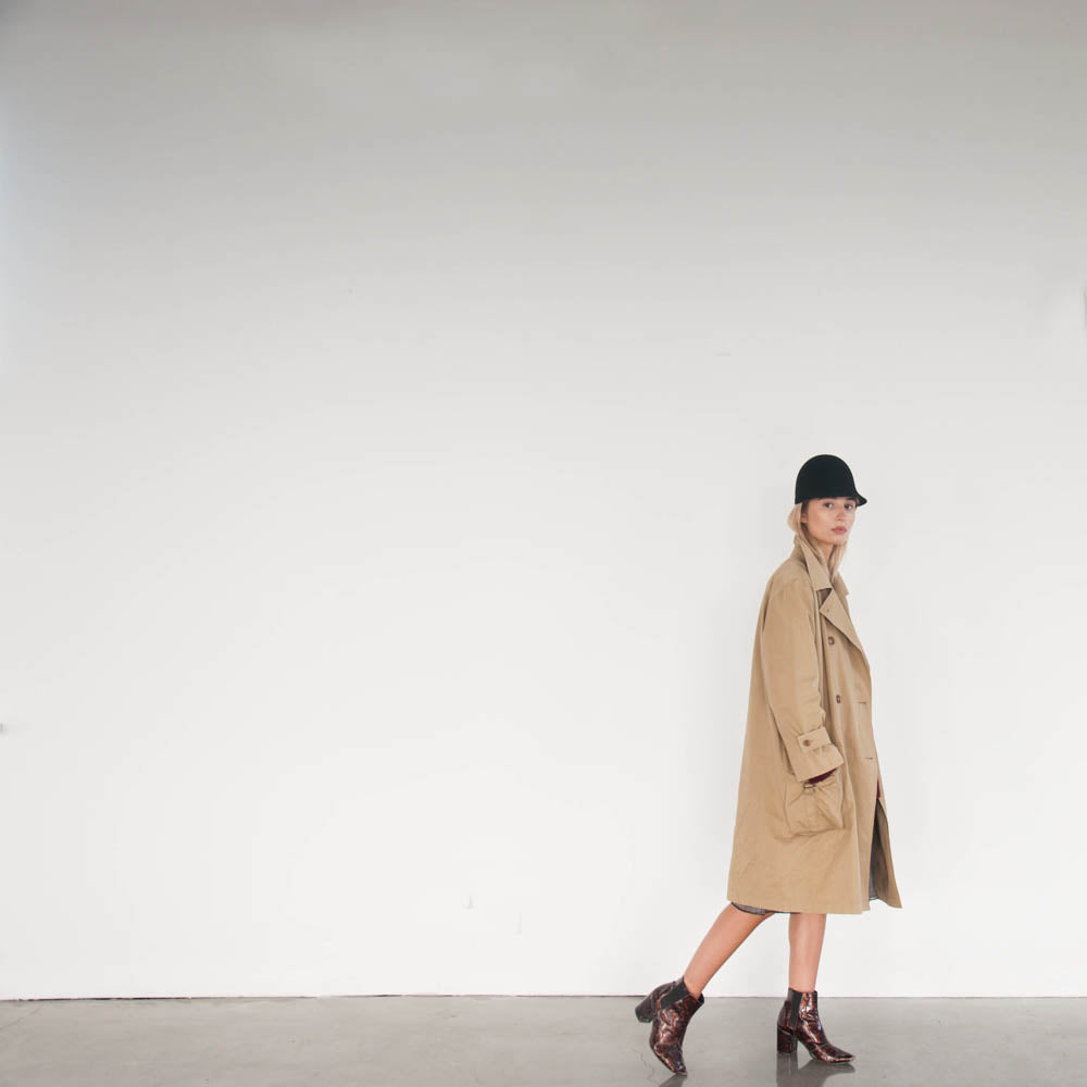 Wearing a long trenchcoat and the felt cap Guerrero, Andrea is modeling for this editorial.