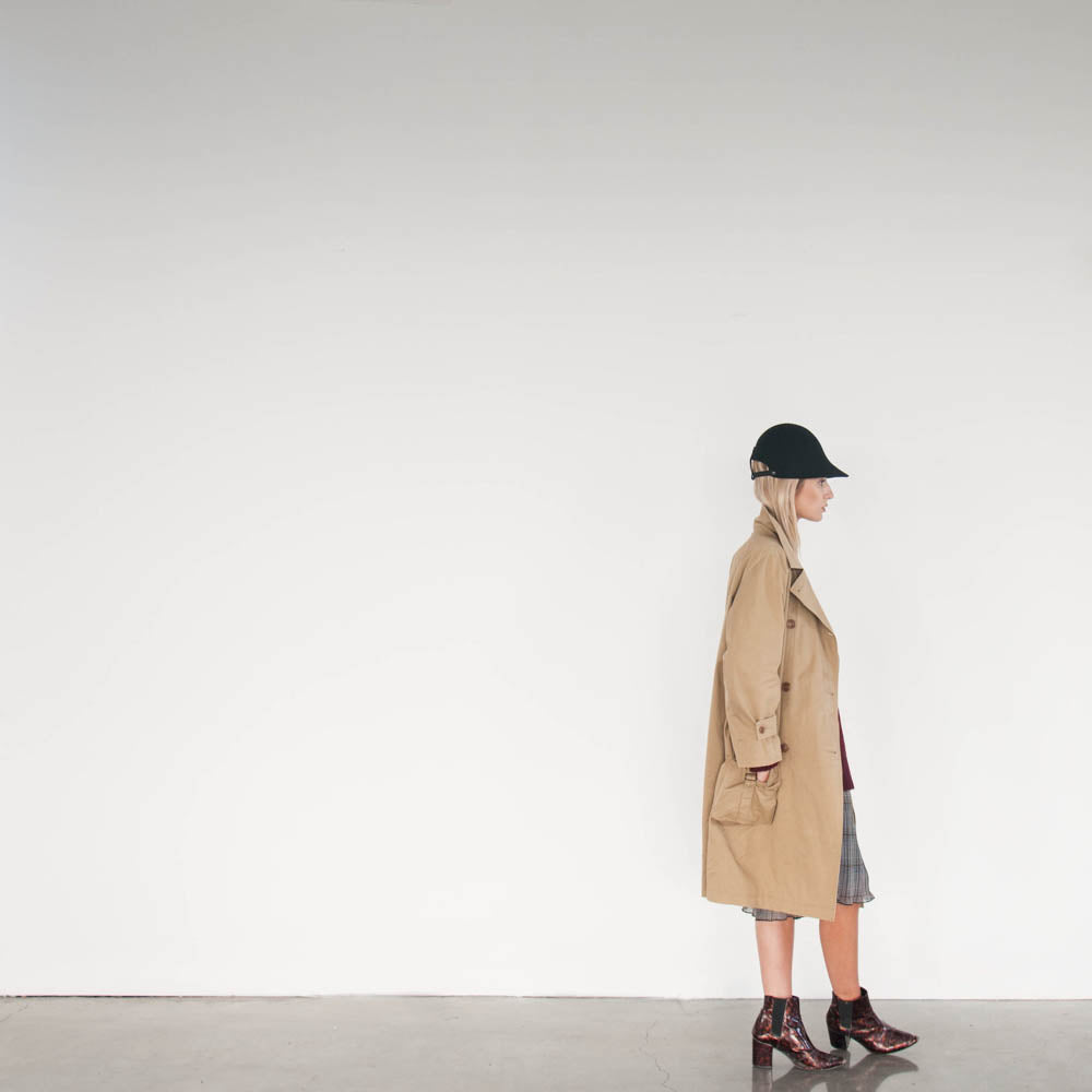 The trenchcoat of Andrea matches the Camille Côté felt cap.