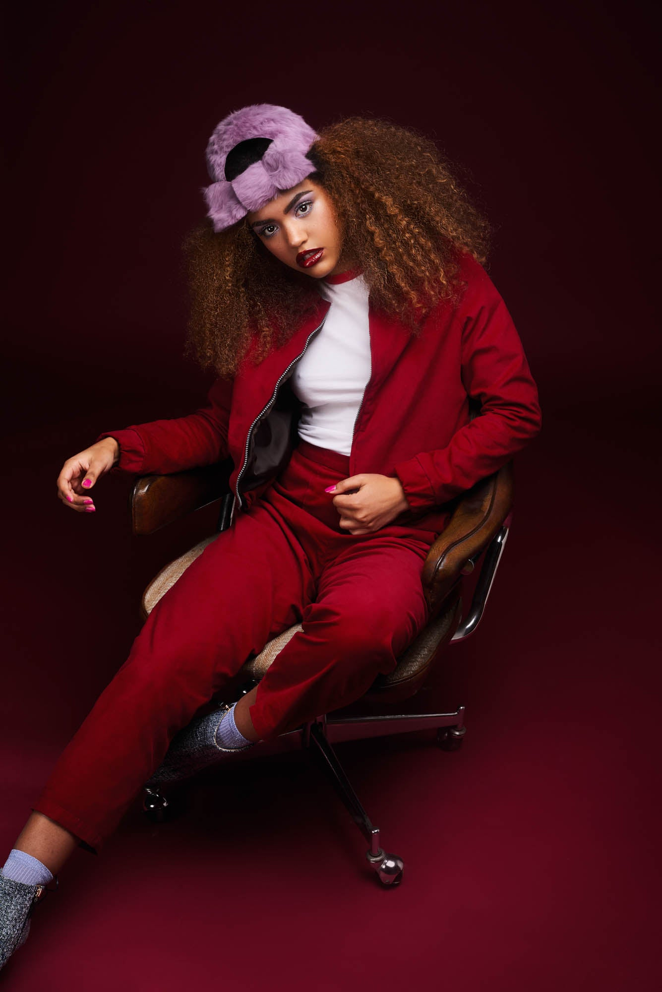 The natural hair model wears a red suit with the purple furfelt knot hat