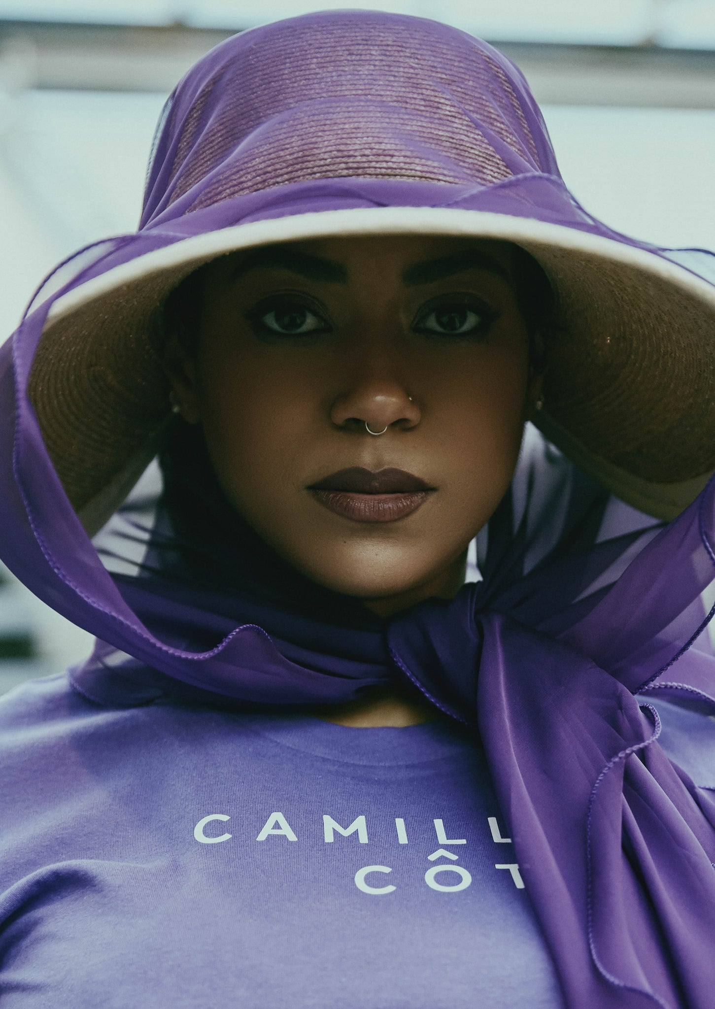 The woman wears a silk scarf with the Camille Côté T-shirt and summer hat.