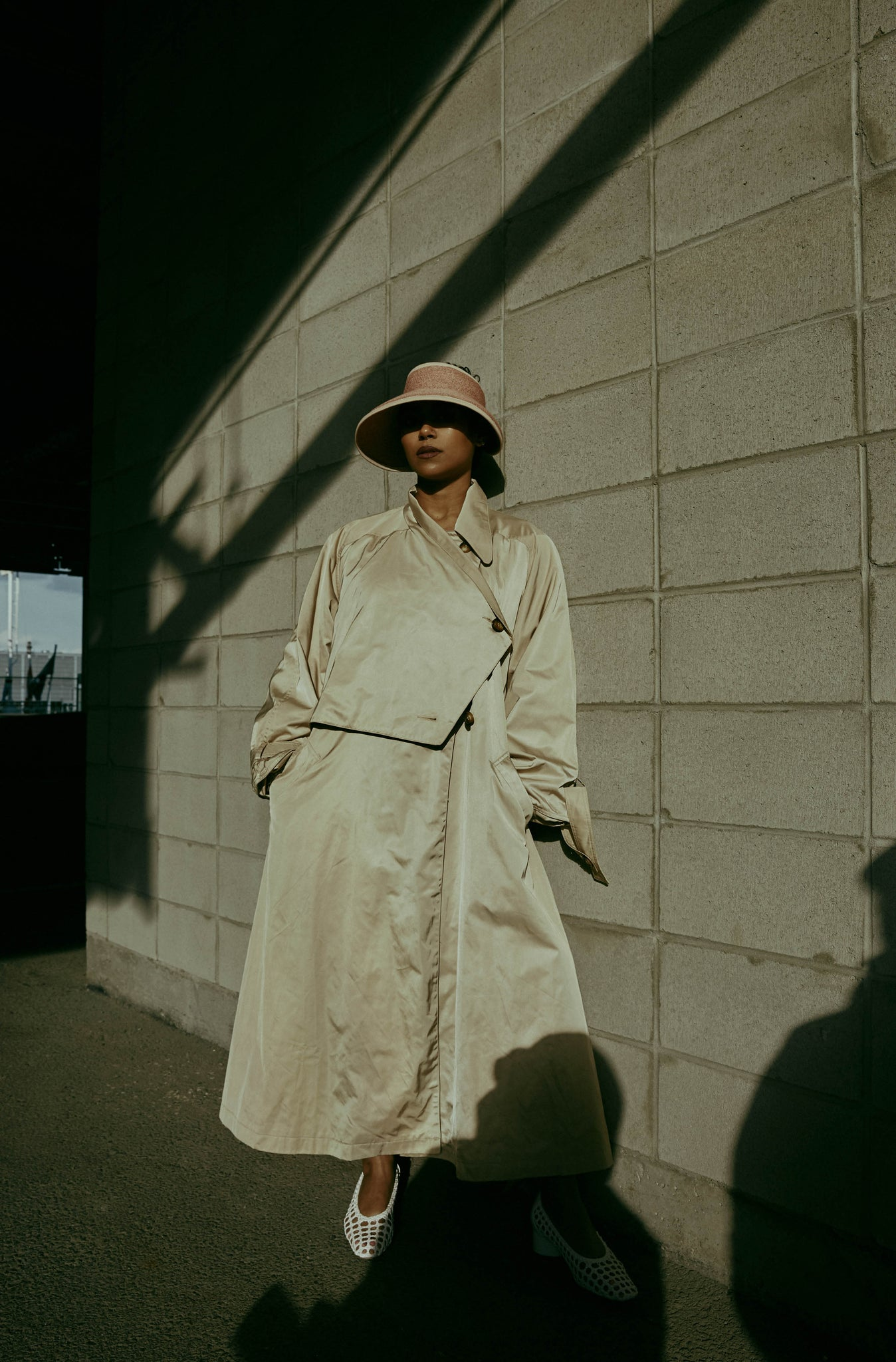The woman wears a beige trench with the pink visor Brigitte.