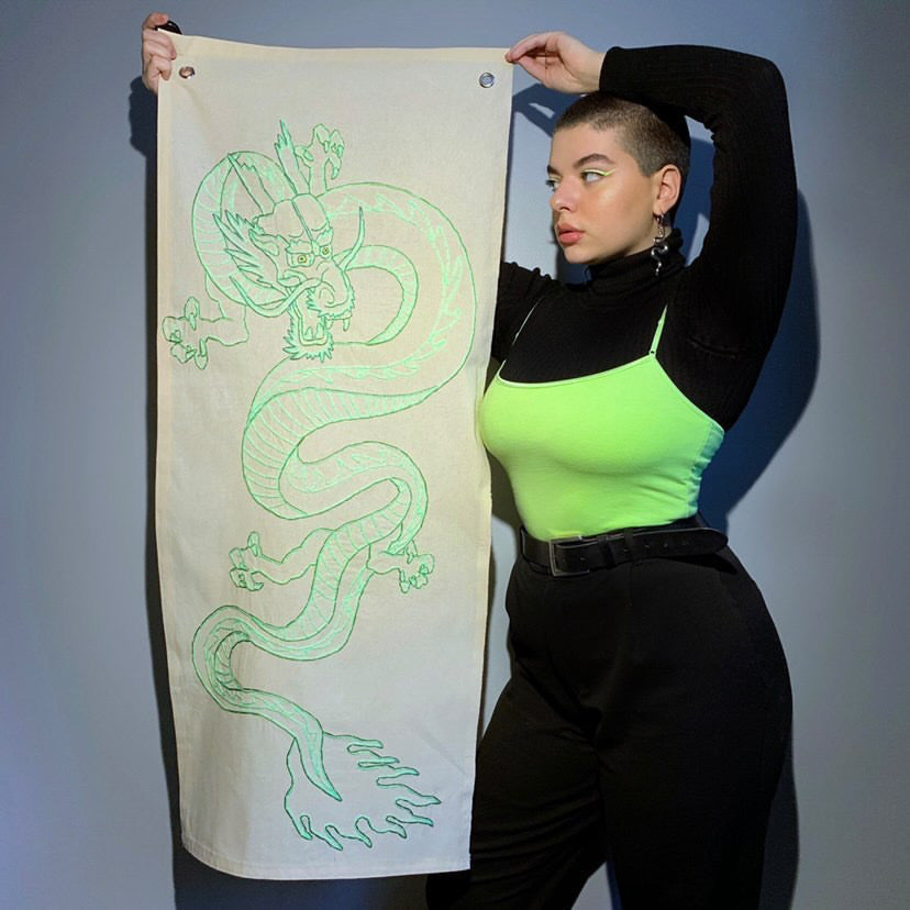 Short hair model wearing a black turtleneck with a neon green camisole, standing next to her embroidery art