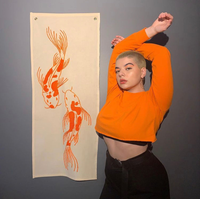 Short hair model wearing an orange crop sweater, standing next to her embroidery art
