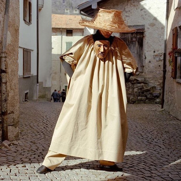 Model dancing in a long beige robe with a big straw hat, taking off @maggieontherocks's Instagram account