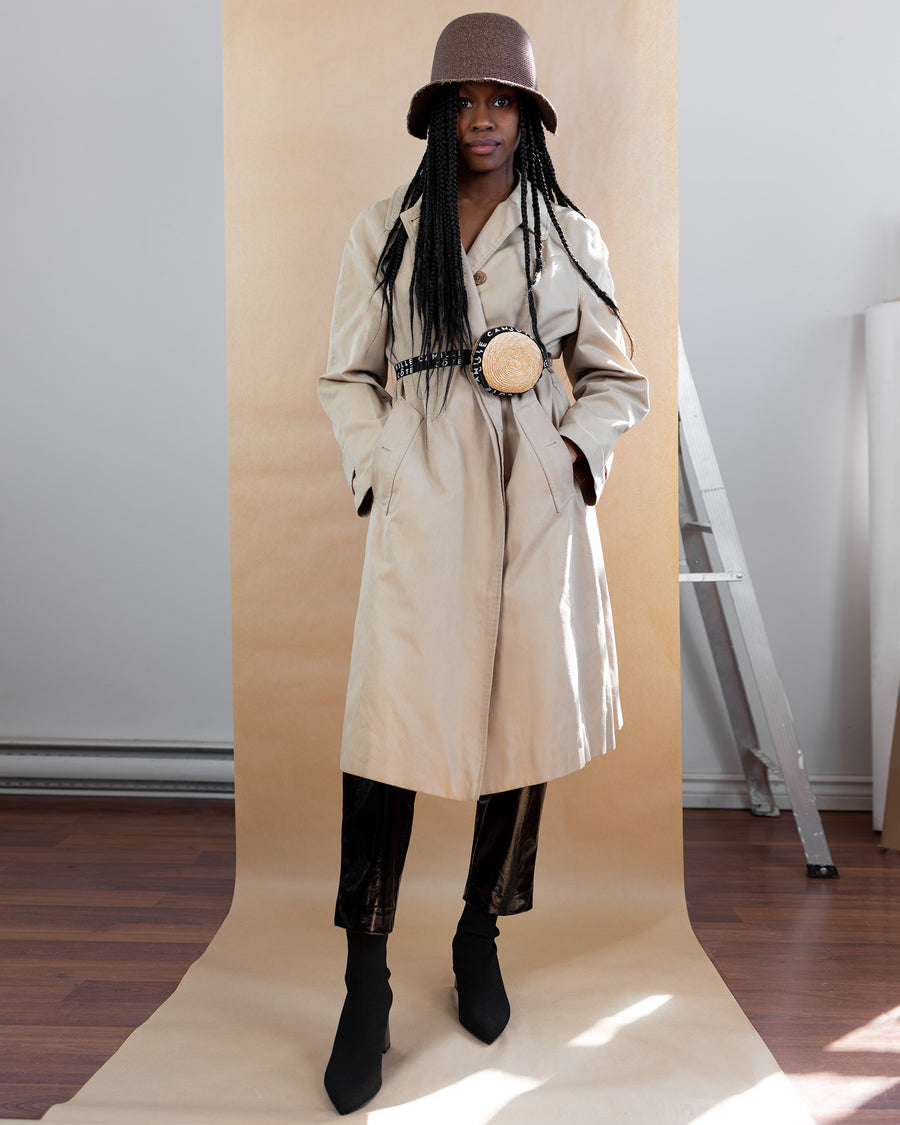 The model wear a beige trench coat with a Camille Côté belt bag and the DAVIS hat