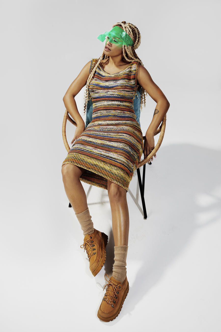 Long curly hair model DJ Karaba, wearing a green see-through visor, with a mid-length multicolor striped knitted dress, long beige knitted socks and worker boots