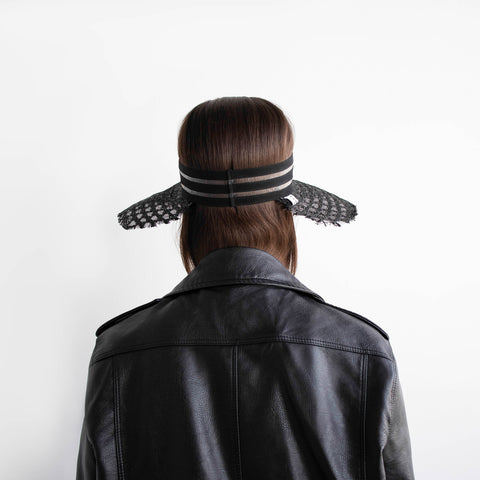 The model wear a black leather jacket with the wide straw visor AIMÉE.