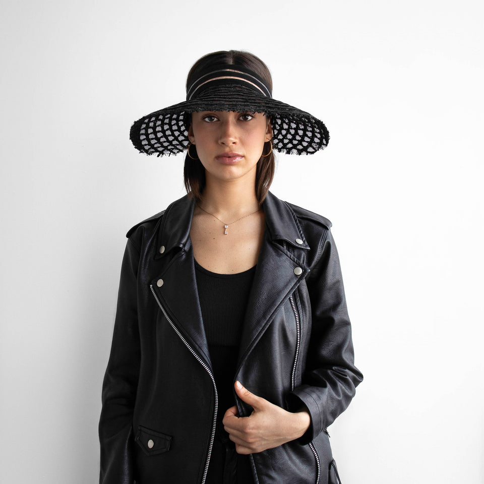 The model is wearing the black wide brim visor AIMÉE