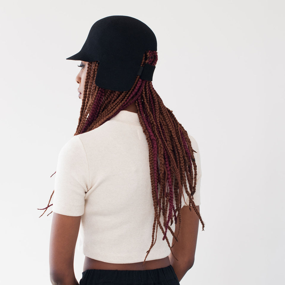 The model wearing the black felt hat BABE with integrated elastics on the back.