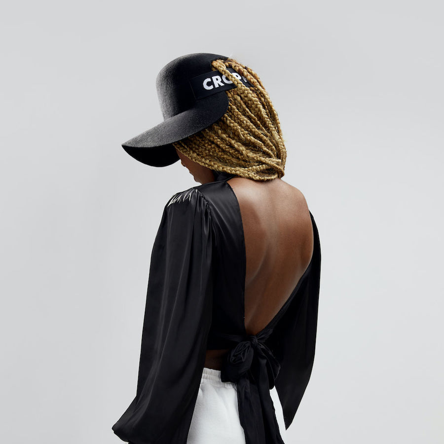 The black felt Cropped Hat™ fits this braided hair model.