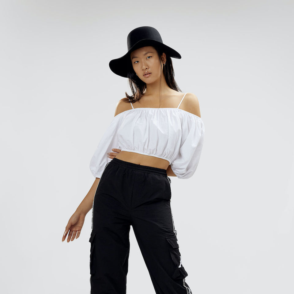 The black felt hat is weared with a black and white outfit by the model.