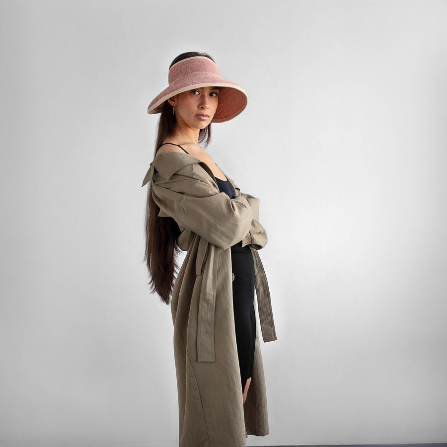 The model wear a beige trenchcoat with the pink visor brigitte by Camille Côté.