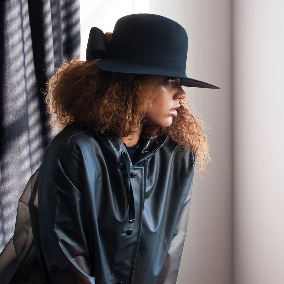 The natural hair model wear the black bronx hat from Camille Côté's collection.